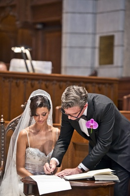 bride in pnina tornai and groom in tux and purple orchid boutonniere sign marriage license