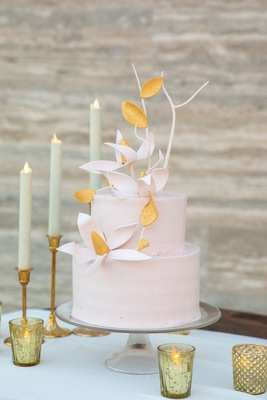 wedding cake on glass cake stand two layer round cake pink with sugar flowers branches gold taper