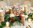 Winter wedding reception table with Dickens' Village Series house, evergreen, white roses, red