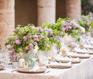wedding reception long table outdoor destination wedding italy low centerpiece greenery purple lilac