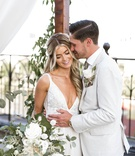 bride in v neck wedding dress long hair boho style groom in casual suit white flowers greenery