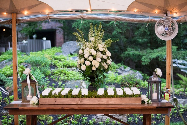 Wood table with planter box green grass leaf sprigs escort cards white flower arrangement lantern