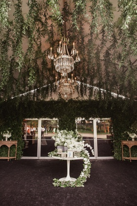 reception tent with hanging greenery all over tented area and tables