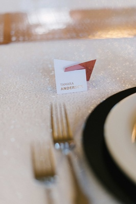 Small contemporary style escort card on a shimmering white table linen