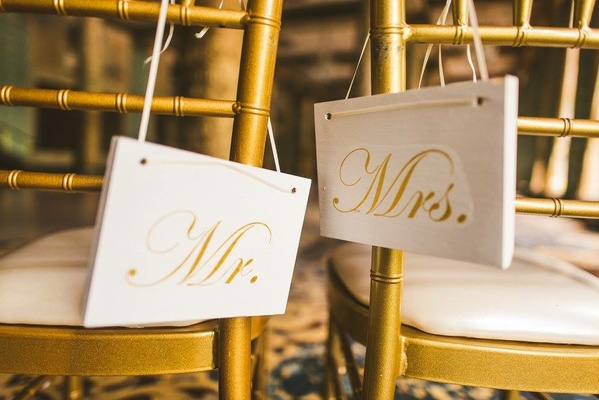 wedding reception decoration gold chair white cushion white gold calligraphy rectangle sign ribbon