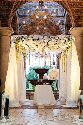 Jewish wedding ceremony with chuppah covered with ivory fabric, decorated with white flowers