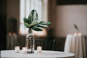 wedding reception white candle votive unique glass vase with greenery leaves tropical jungle plants