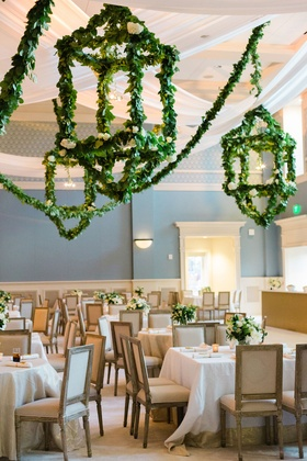 Wedding reception greenery garland lanterns overhead square tables wood chairs white flowers