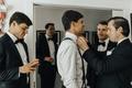best man adjusting the groom's bow tie, groomsmen getting ready pictures