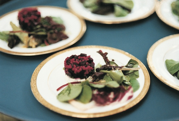 Gold rimmed plate topped with beet and goat cheese salad