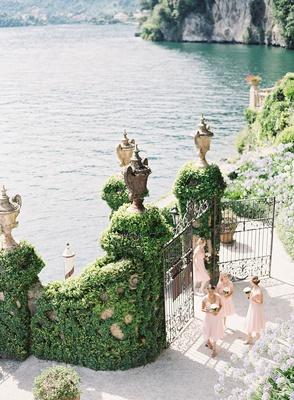 bridesmaids and flower girls walking up boat dock to entrance of villa del balbianello lake como