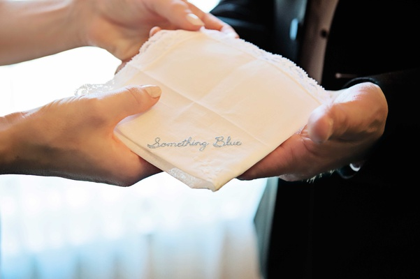 white and blue handkerchief with the phrase something blue embroidered onto it