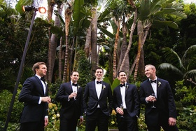 Tuxedo groom and groomsmen in front of palm trees