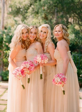 Bridesmaids in strapless gowns and curled hair