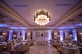Purple uplighting banquet hall wedding reception sweetheart table with overflowing flower runner