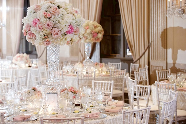 Round wedding reception table with crystal vase pink rose and white hydrangea flowers white chairs