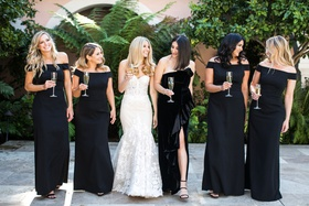 bride in strapless inbal dror mermaid wedding dress with bridesmaids black dresses off shoulder slit