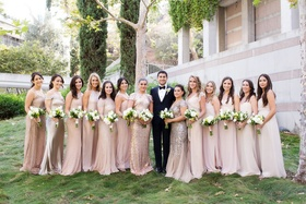 Groom in tuxedo with bridesmaids in mismatched champagne dresses with white bouquets