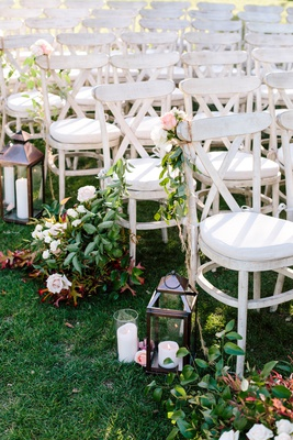 white-washed ceremony chairs adding a rustic look, lantern aisle decoration, greenery