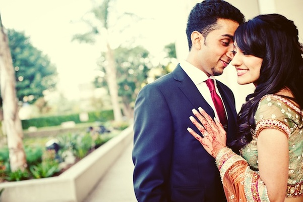 Indian woman with henna and man in suit with red tie
