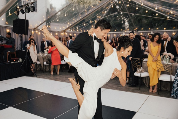 bride in one shoulder jumpsuit for first dance cool lift dance lessons groom holding bride tent