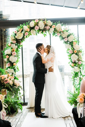 bride grabs groom by the face for first married kiss under floral arch