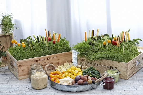 Wood boxes filled with grass and veggies on toothpicks