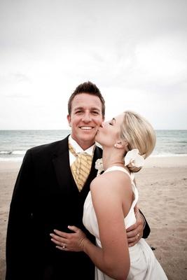 Bride kisses groom's cheek on beach in Florida