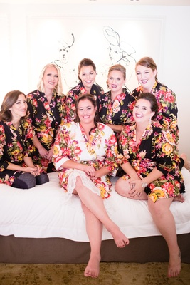 bridesmaids in black floral bridesmaid robes's bride in white floral robe