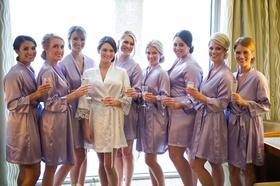 Bridesmaids in purple robes in bridal suite