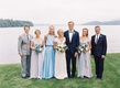 Bride in Carolina Herrera wedding dress with groom in tuxedo by lake with Marriott family bridesmaid