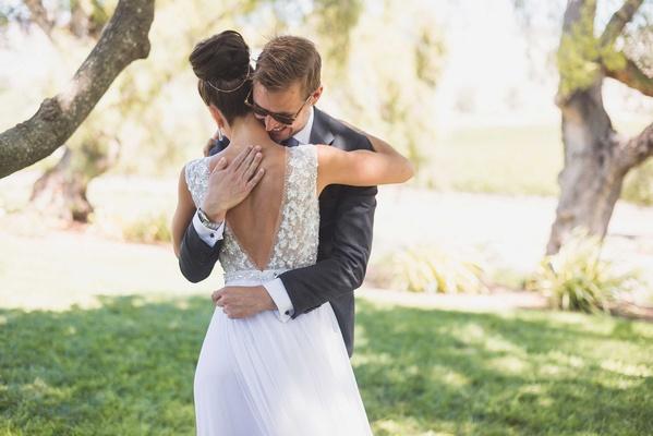 Bride in Mira Zwillinger wedding dress from Carine's Bridal Atelier low v-back high bun hugs groom