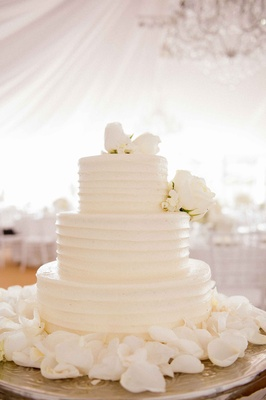 White wedding cake with white roses surrounded by petals from SusieCakes