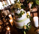 white cake with green fondant ribbon and yellow flowers sits on tree stump surrounded by candles