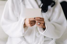 Square cushion cut diamond ring on bride in white bridal robe