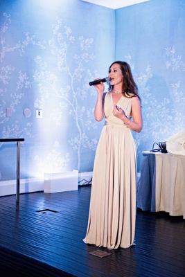 maid of honor in tan bhldn dress sings at reception