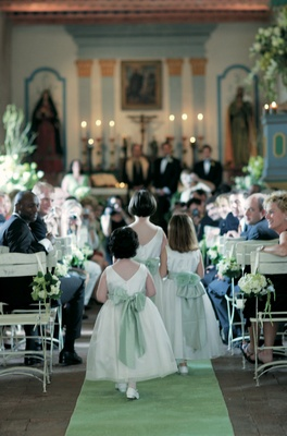 Flower girls in sleeveless white dresses and green sashes