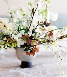 grey vase with amber hellebore, white magnolia, Japanese ranunculus