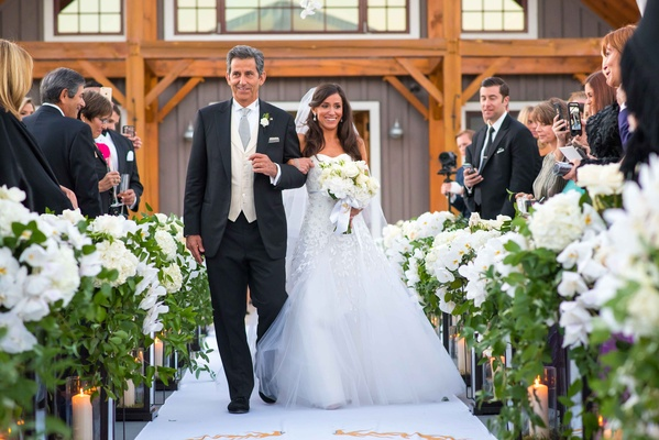 Bride in Carolina Herrera wedding dress walking down aisle with father in three piece suit Aspen