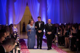 Groom walks down aisle with parents at purple ceremony