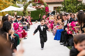cute ring bearer in tuxedo bow tie and sneakers running down aisle flower girl behind