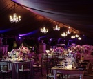Tented dinner space with chandeliers and purple florals