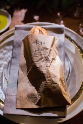 Baguette of bread in kraft paper letterpress menu bag at wedding reception