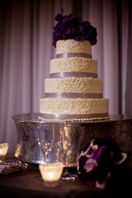 Four layer cake with ribbons and white design