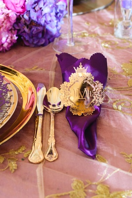 opulent shiny gold napkin ring with monogram around royal purple napkin and gold flatware