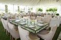 Mirror reception table with upholstered neutral chairs and white flowers at tent wedding reception