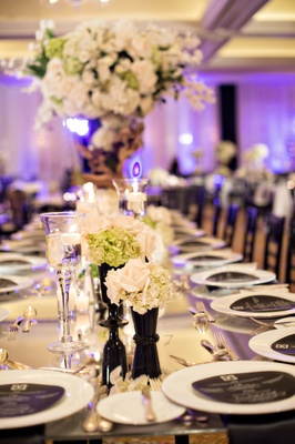 green, white, and black reception décor round menus purple lighting