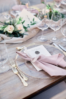 wooden table with gold-rimmed clear charger, blush napkin, gold flatware