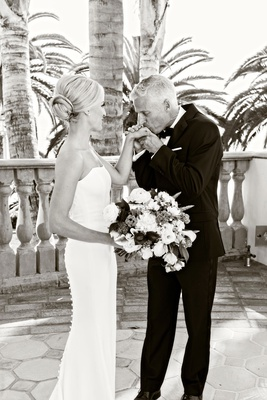 black and white photo of bride in ines di santo wedding dress and father of bride kissing hand