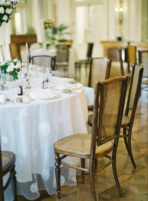 wedding reception lake como villa white round table linen cane back chairs wood floors